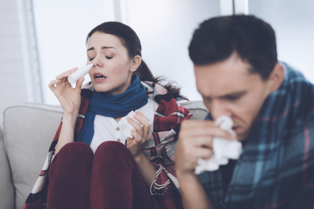 The couple is sitting on the couch wrapped in blankets. Man and woman are sick. They have a bad cold
