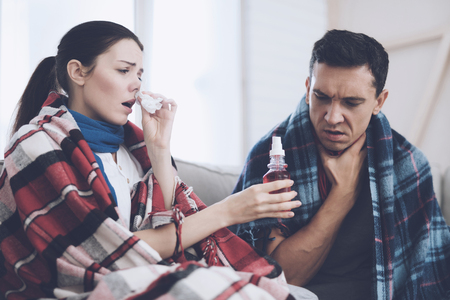 The couple is sitting on the couch wrapped in blankets. Man and woman are sick. The man has a sore throat