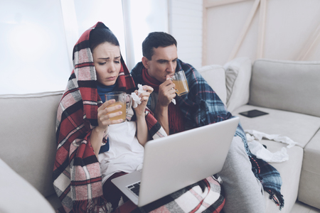 The couple is sitting on the couch wrapped in blankets. Man and woman are sick. They are looking something on the laptop