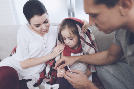 The little girl caught a cold. Her mother and father are treating her. Father gives the girl a pill Stock Photo - 89826666