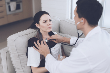 The woman fell ill and called the doctor at home. She sits on the sofa with a blanket. Doctor listens to her stethoscope