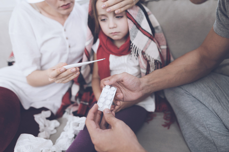 The little girl caught a cold. Her mother and father are treating her. Mother holding a thermometer. Father holds pills