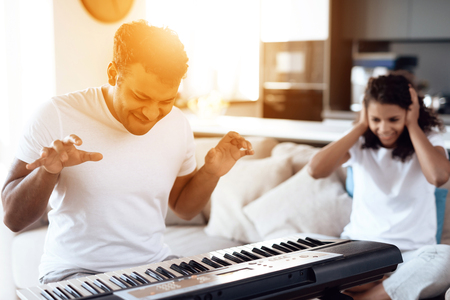 A black man sits in the living room of his apartment and plays a synthesizer. A girl sits next to him, covering her ears
