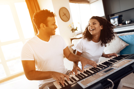 A black man sits in the living room of his apartment and plays a synthesizer. A girl is sitting next to him.
