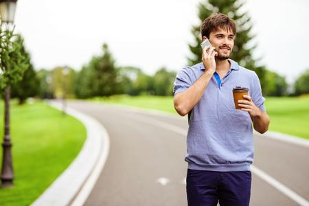 Een man rijdt door het park op een gyroboard. Hij is aan het telefoneren en houdt een glas koffie