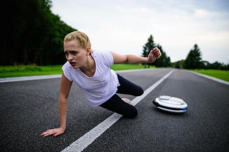 女性は一輪車で公園の小道に沿って運転していた、落ちた。痛いです 写真素材