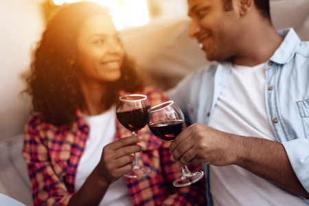 Black man and woman are sitting on the couch. A man and a woman embraced and drank wine.