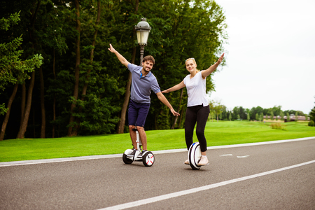 The couple is riding a gyroboard and a monocle in the park. They are happy. They go with their arms apart and look happily. Against the background of a beautiful park Stok Fotoğraf
