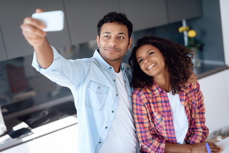 Black man and woman in the kitchen at home. They prepare and make selfi while preparing food.