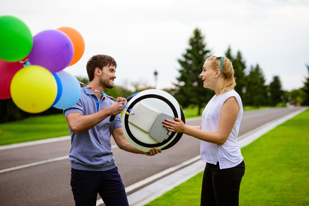 A man gives his girl a monocle. Inflatable balls are attached to the gadget. She is happy