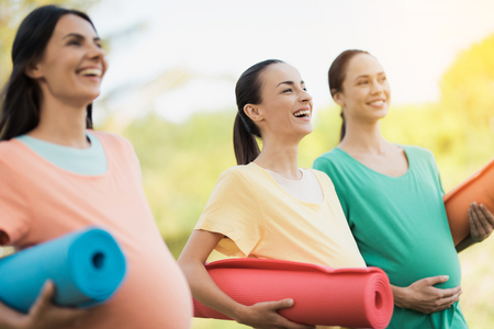 Three pregnant girls posing in a park with yoga mats in hand. They smile and have fun Stock Photo