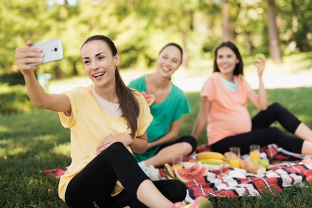 A pregnant woman in a yellow T-shirt sits with her pregnant girlfriends on a picnic in the park and makes a selfie Stock Photo