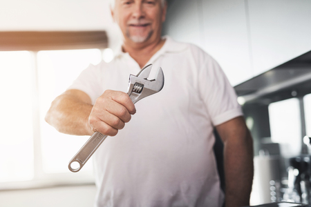 The man is in the kitchen. He has a chrome wrench in his hand. Next to him is a tool box. Stock Photo