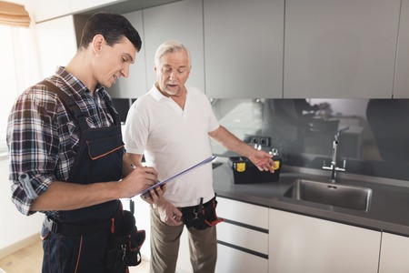 Two men of plumbers are standing in the kitchen. An elderly man inspects the place of repair work.
