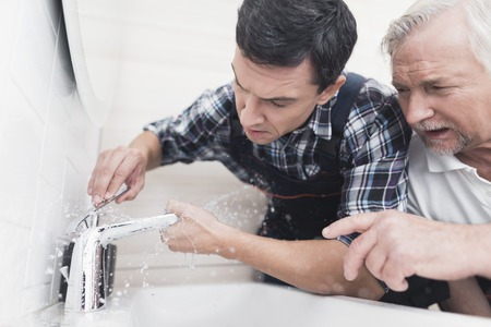 Two plumbers repair the faucet in the bathroom. One of them replaces the tap, the second one teaches the junior.