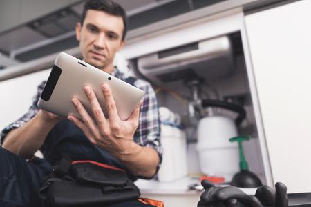 Le plombier est assis à côté de l'évier de la cuisine et regarde la tablette pour des instructions de réparation.
