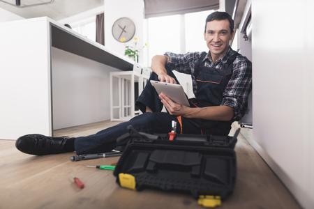 配管工床に台所の流しの隣に座っていると修理手順のタブレット。 写真素材