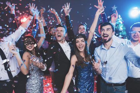 Jonge mensen hebben plezier op een nieuwjaarsfeest. Om hen heen vliegt confetti. Ze hebben plezier. Stockfoto