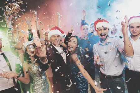 I giovani si divertono ad una festa di Capodanno. Attorno a loro volano i coriandoli. Archivio Fotografico - 89936903