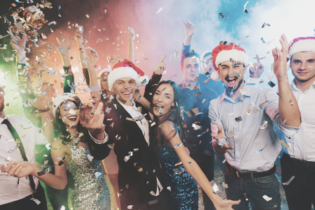 Young people have fun at a New Years party. Around them flies confetti. Stock Photo