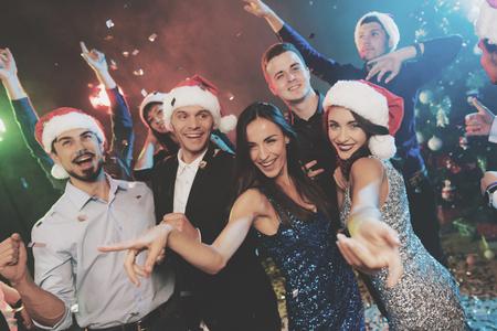 I giovani si divertono ad una festa di Capodanno. Attorno a loro volano i coriandoli. Archivio Fotografico - 90082853