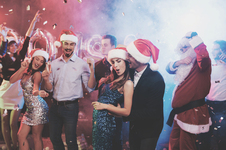 Young couple having fun at New Years party. They dance in santa claus caps.