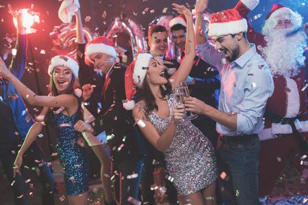 Giovani coppie che ballano con bicchieri di champagne in mano. Dietro di loro ballano i loro amici e l'uomo vestito da Babbo Natale. Archivio Fotografico - 89974087