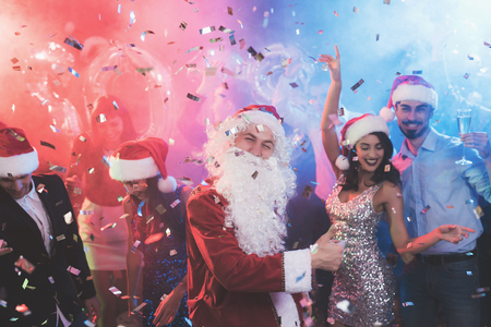 A man dressed as Santa Claus has fun at a New Year party. Together with him have fun friends. Stock Photo