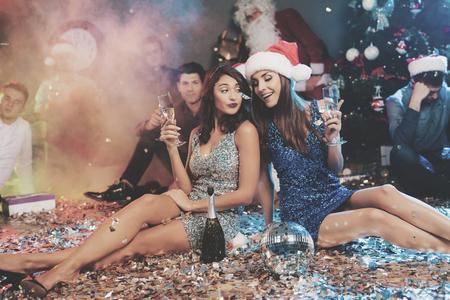 二人の女の子が床に座っています。彼らの周りには、紙吹雪が散在しています。彼らは新年のパーティーの後休む