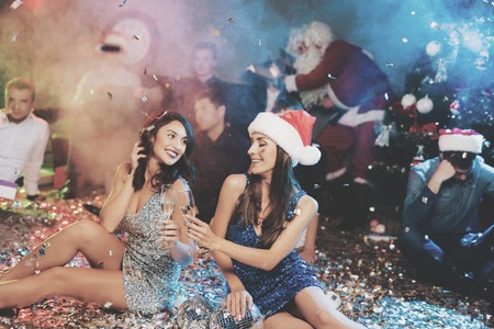 Two girls are sitting on the floor. Around them is scattered confetti. They rest after the party for the new year