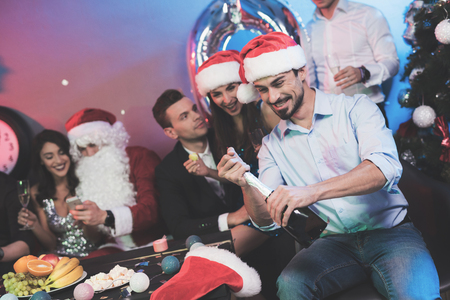 A man in a Santa Claus hat opens a bottle of champagne. A mans friends sit next to him and a guy dressed as Santa Claus