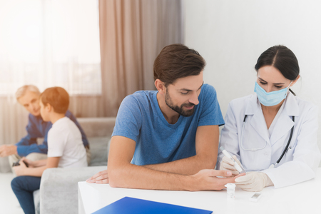 A nurse takes a blood sample from a man with a scarifier. A nurse is sitting in a mask and gloves at the table. Stock Photo