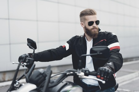 A young guy with a beard sits on his electric motorcycle. Reklamní fotografie - 90134441