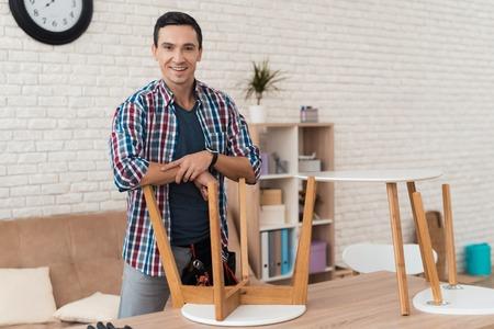 その若者はコーヒーテーブルとスツールを折りたたもうとします。