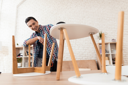 The young man tries himself to fold his coffee table and stools.