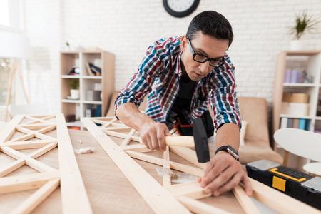 De jongeman probeert zichzelf zijn boekenkast te vouwen. Stockfoto - 89995000