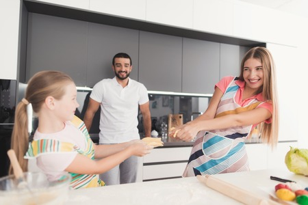 La famiglia cucina l'impasto per la cottura. La mamma e la ragazza stanno preparando un impasto, lo imbrogliano e lo strappano.