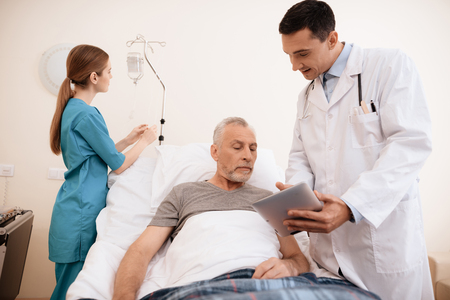The old man lies on a cot in medical ward, and next to him stands a doctor. He is showing something to old man on tablet Stock Photo