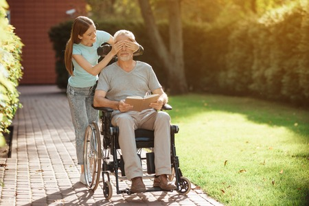 An elderly man is sitting in a wheelchair. The girl stands behind him and closes his eyes. The old man is reading book. Stock Photo