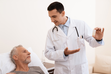 The old man lies on a cot in the medical ward, and next to him stands a doctor. He explains something to the old man.
