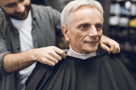 The old man is sitting in the barbers chair in a mans barbershop, where he came to cut his hair.