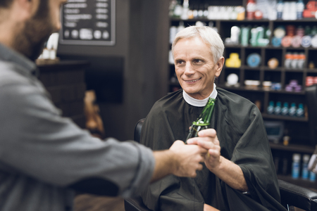 The old man drinks alcohol in the barbers chair in barbershop.