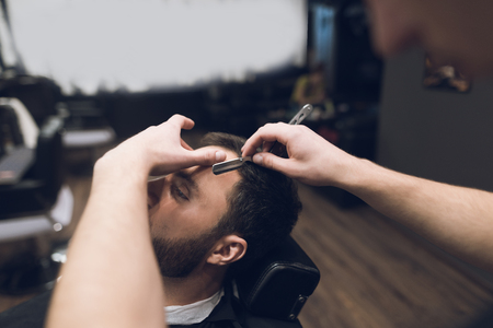 The barber shaves his head, mustache and beard to the man in the barbershop.
