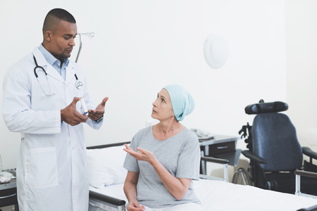 The doctor gives the woman a pill. A woman undergoes rehabilitation after cancer treatment.