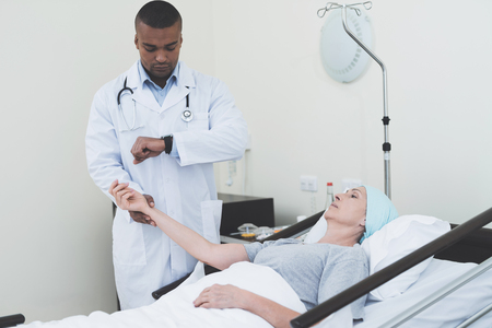 The doctor is measuring the pulse of a woman. A woman undergoes rehabilitation after cancer treatment.