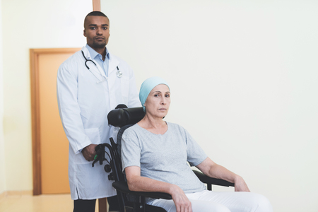 The doctor takes a woman to the ward who undergoes rehabilitation after treatment for cancer.