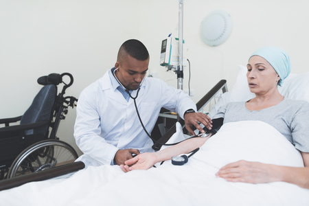 The doctor measures the pressure on the woman. A woman undergoes rehabilitation after cancer treatment.