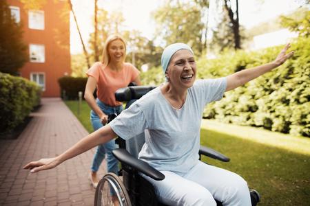 癌を持つ女性は、車椅子に座っています。彼女は彼女の娘と一緒に通りに歩くし、彼らが浮気します。
