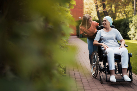A woman with cancer is sitting in a wheelchair. She walks on the street with her daughter and they are having fun.