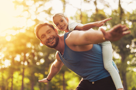 Father and daughter fool around in the park. A man rolls a girl on her shoulders